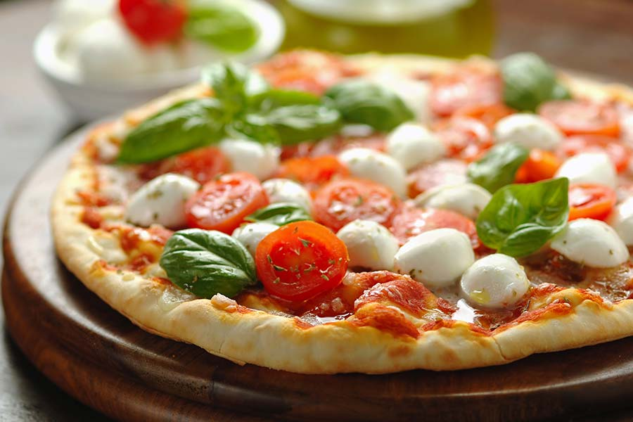 Pizza with fresh basil, pachino tomatoes and buffalo mozzarella