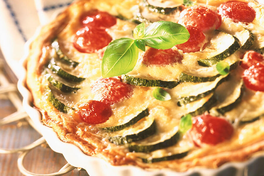 Torta di zucchini e pomodori guarnita con basilico